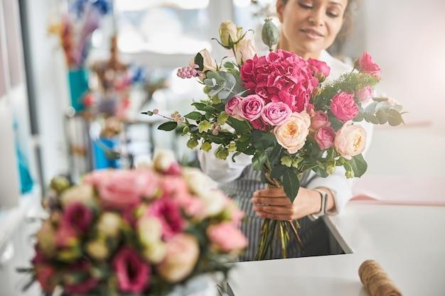 Professionele bloemist poseren met een prachtige bloemencompositie