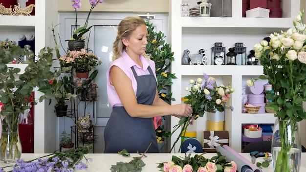Professionele bloemistvrouw maakt een prachtig bloemboeket met rozen, bladeren en gipskruid. blonde vrouw van middelbare leeftijd in uniform werkt in bloemenwinkel. ze maakt een heleboel tedere kleuren roze en geel.