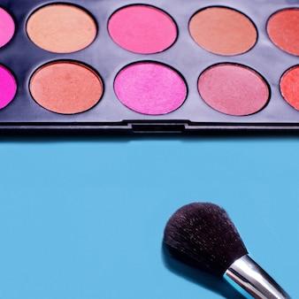 Professionele blush borstel en gereedschap, make-up producten op een blauwe achtergrond. make-up set. plat leggen, ruimte kopiëren, achtergrond voor ontwerp