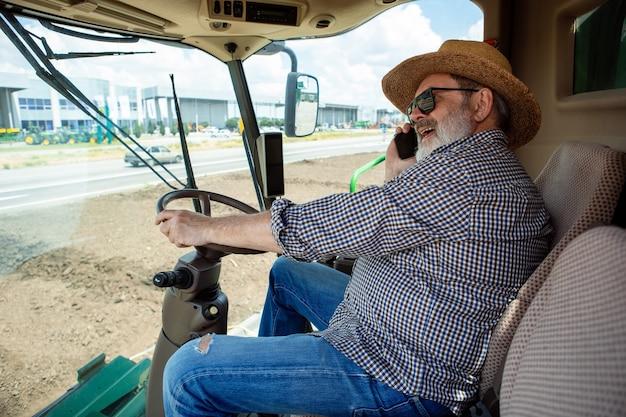 Professionele boer met een moderne maaidorser op het werkproces. ziet er zelfverzekerd uit, felle zomerkleuren, zonneschijn. landbouw, tentoonstelling, machines, plantaardige productie. senior man rijdt op tractor.