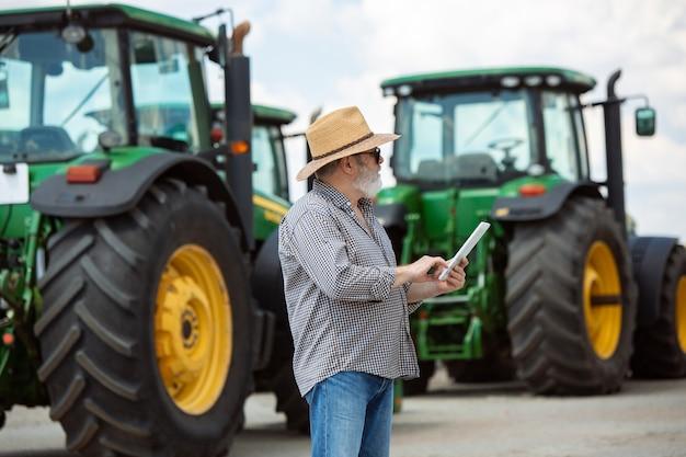 Professionele boer met een moderne tractor aan het werk met tablet. ziet er zelfverzekerd uit, felle zomerkleuren, zonneschijn. landbouw, tentoonstelling, machines, plantaardige productie. senior man in de buurt van zijn machine.