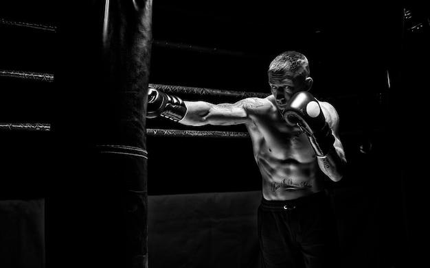 Professionele bokser slaat de tas tegen de achtergrond van de ring. zijaanzicht. het concept van sport en klassiek boksen. gemengde media