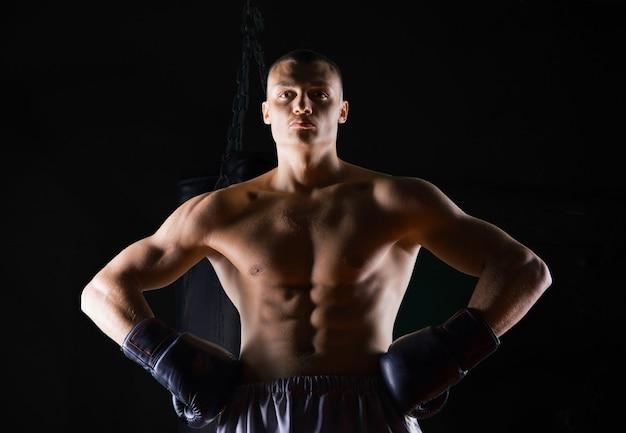 Professionele bokser staat in de sportschool en kijkt zelfverzekerd naar de camera