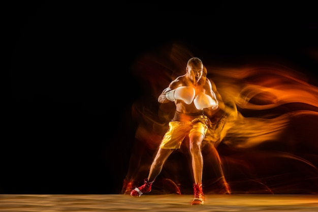 Professionele bokser training geïsoleerd op zwarte studio achtergrond in gemengd licht