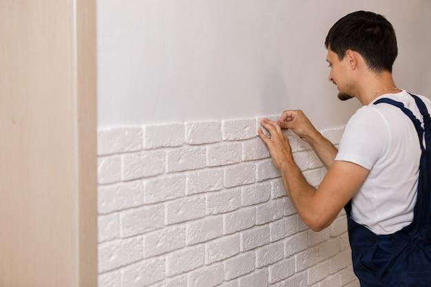 Professionele bouwer die decoratieve tegels op muur lijmen. werknemer monteert decoratieve baksteen op de muur