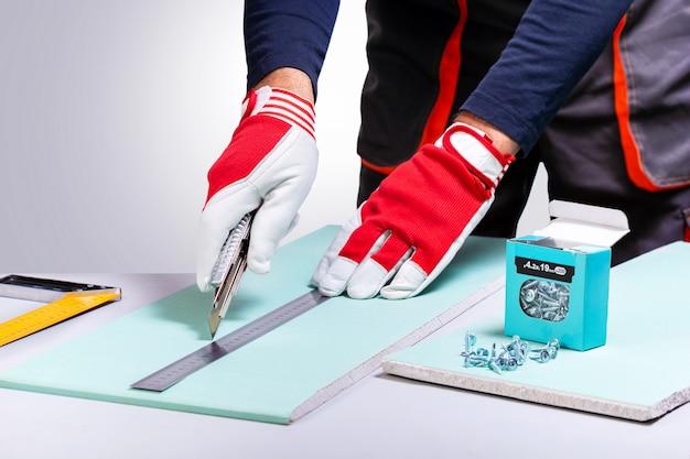 Professionele bouwer die met gipsplaat werkt. man gipsplaat snijden met mes. home reparatie concept.