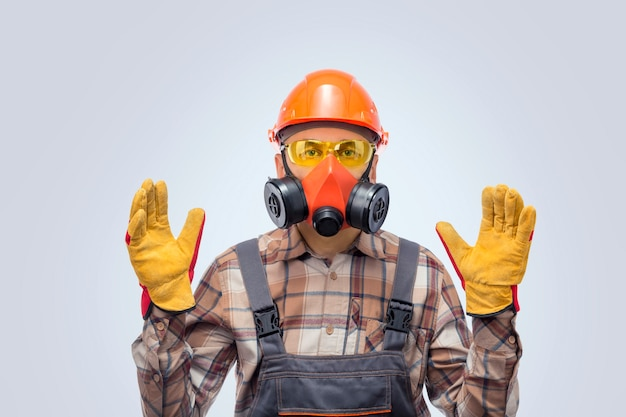Professionele bouwer in veiligheidsuitrusting over grijze achtergrond. persoonlijke beschermingsmiddelen.