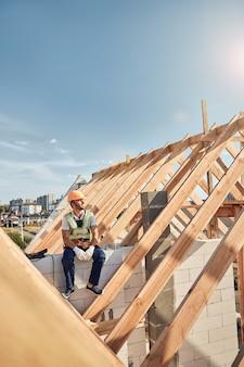 Professionele bouwer met een helm en een goed zichtbaar vest, zittend op een bakstenen muur en rustend