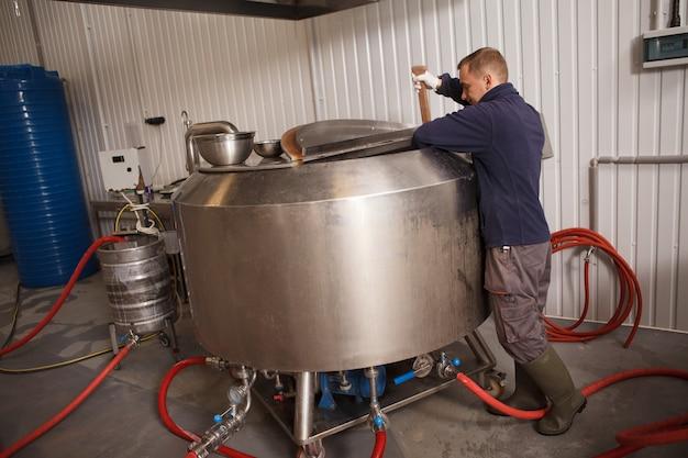 Professionele brouwer werken bij bierfabriek bier in brouwtank controleren