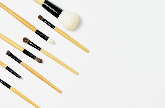 Professionele bruine, houten make-upborstels liggen schuin naar links. make-up borstel geïsoleerd op een witte achtergrond. horizontale sjabloon voor visagist visitekaartje of flyer ontwerp.