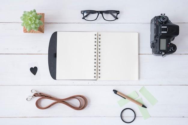 Professionele camera; lege spiraalvormige blocnote; schouwspel; plakbriefjes; riem; pen; heartshape en vetplant op witte houten tafel