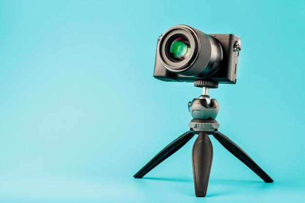 Professionele camera op een statief, op een blauwe achtergrond. neem video's en foto's op voor uw blog of rapport.