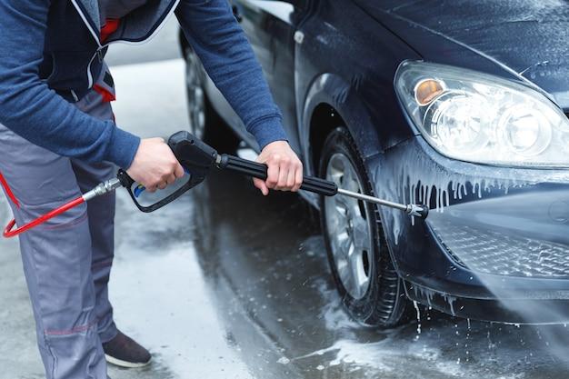 Professionele carwash werknemer wast de auto van de klant