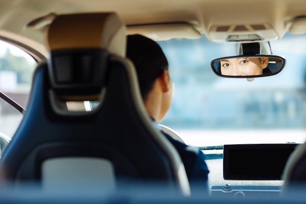 Professionele chauffeur. leuke prettige vrouw die in de achteruitkijkspiegel zit terwijl ze achter het stuur zit