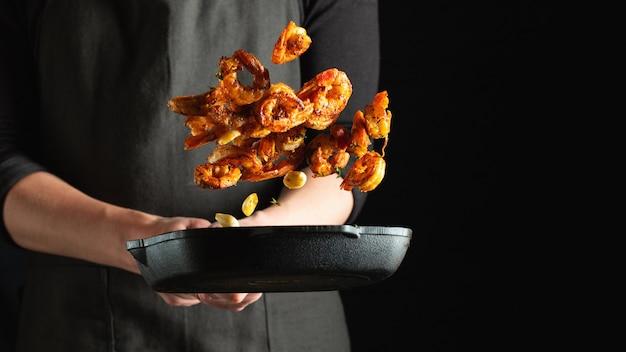 Professionele chef-kok bereidt garnalen of langoustines