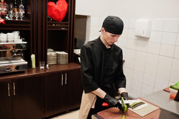 Professionele chef-kok draagt in het zwart sushi en broodjes in een restaurantkeuken van japans traditioneel eten.
