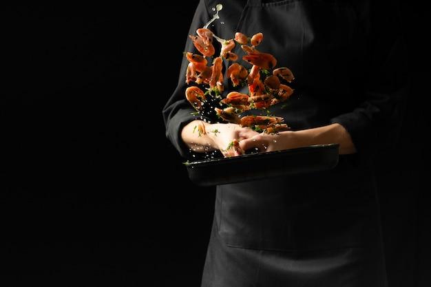 Professionele chef-kok gekookte garnalen. culinaire zeevruchten en voedsel op een donkere achtergrond.