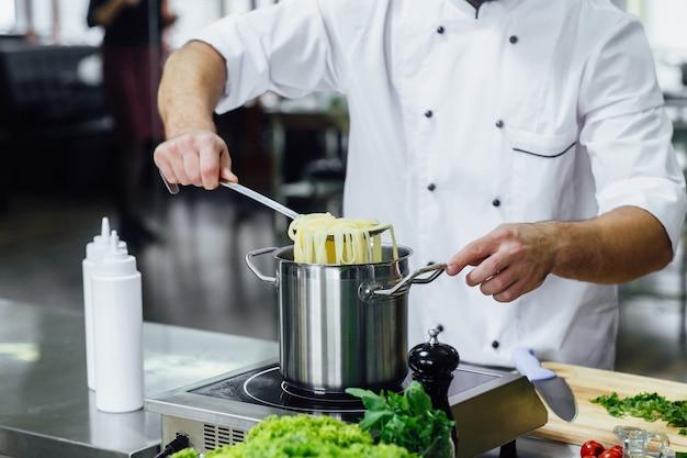 Professionele chef-kok in wit unifirm, kook spahhetti, keukenapparatuur