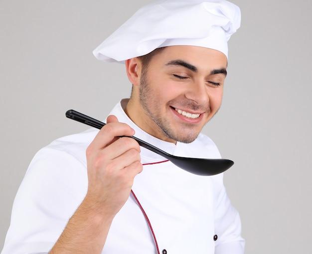 Professionele chef-kok in wit uniform en hoed, op grijs