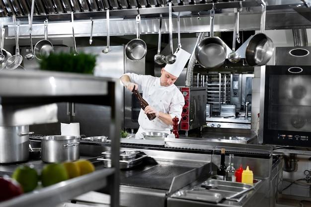 Professionele chef-kok in witte uniforme zouten koningsgarnalen