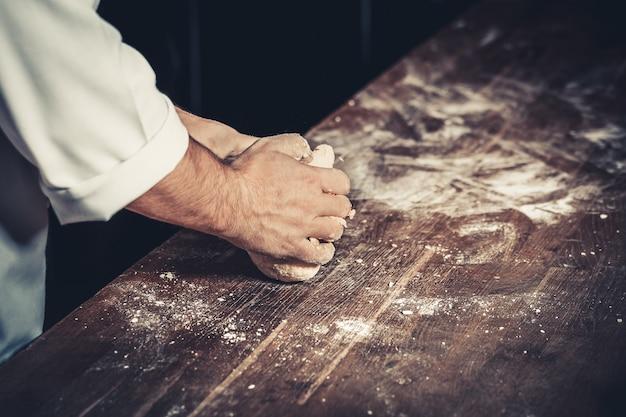 Professionele chef-kok kneedt het deeg voor pizza op een houten tafel. meel rond. alleen handen, close-up