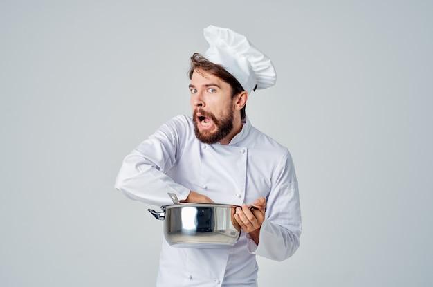 Professionele chef-kok met een pan in zijn handen die voedsel kookwerk probeert