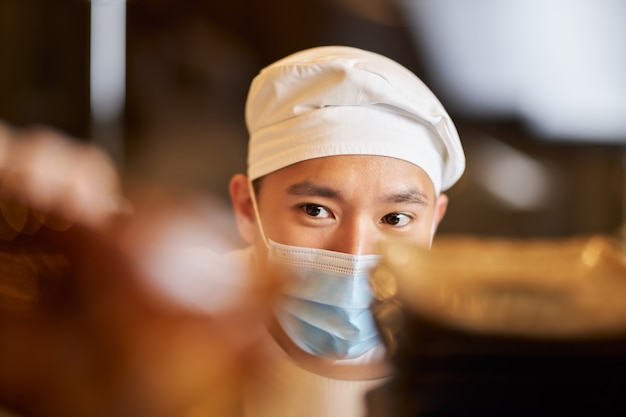 Professionele chef-kok met persoonlijk beschermend masker op het werk