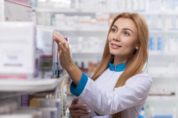 Professionele chemicus die voorraad in een doorgang controleren, die bij de drogisterij werken
