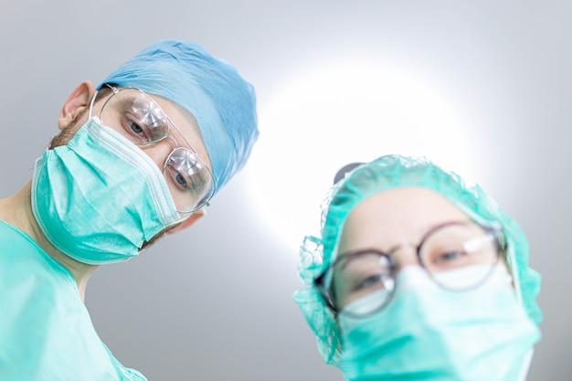 Professionele chirurg met een jonge vrouwelijke assistent-stagiair in een operatiekamer in een ziekenhuis geschoten vanuit een
