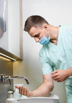 Professionele chirurg wast zijn handen in de kliniek vóór de operatie van de operatie