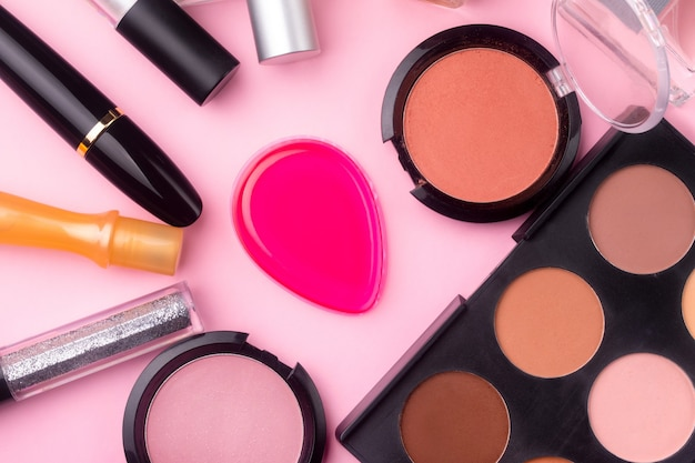 Professionele cosmetica op roze achtergrond. plat lag, make-up achtergrond. cosmetische producten