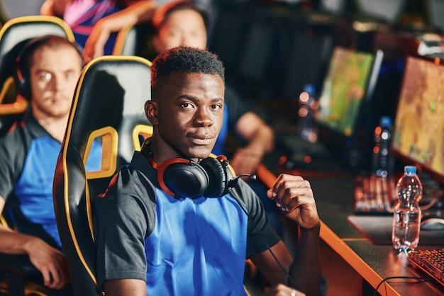 Professionele cybersport-gamer die naar camera kijkt met serieuze gezichtsuitdrukking die deelneemt met