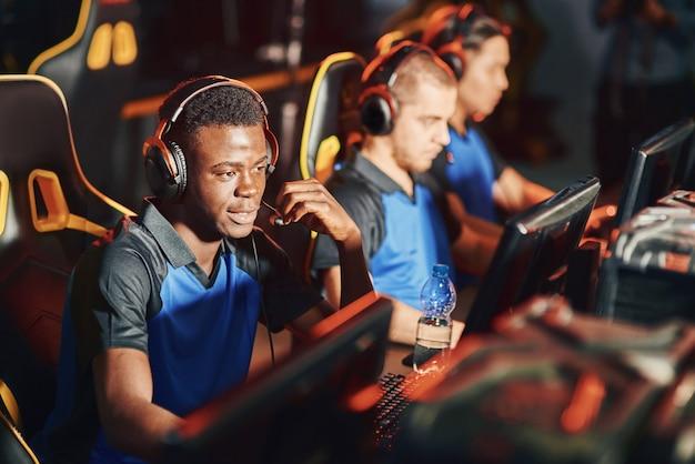 Professionele cybersport-gamer met een koptelefoon die via de microfoon met een teamlid praat terwijl