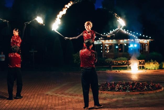 Professionele dansers mannen en vrouwen maken een vuurshow en pyrotechnische prestaties