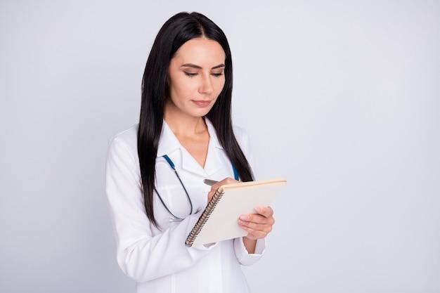 Professionele doc-dame die patiëntsymptomen in voorbeeldenboek schrijft