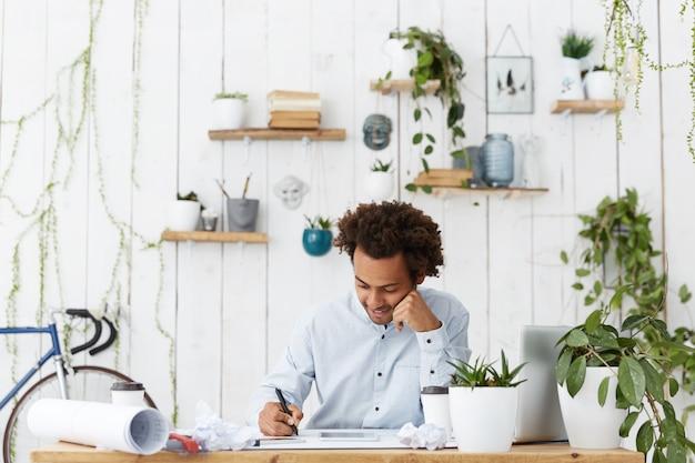 Professionele donkere architect man met afrikaanse kapsel gekleed in formeel wit overhemd