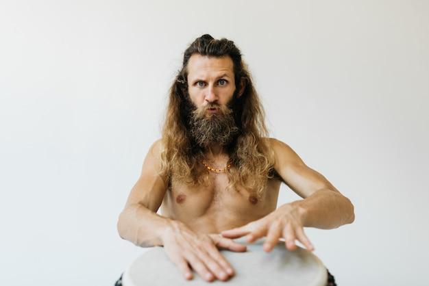 Professionele drummer met baard, snor en lang haar die djembe drum speelt. portret van bekwame musicus die met percussie-instrument muziek maken die op achtergrond wordt geïsoleerd