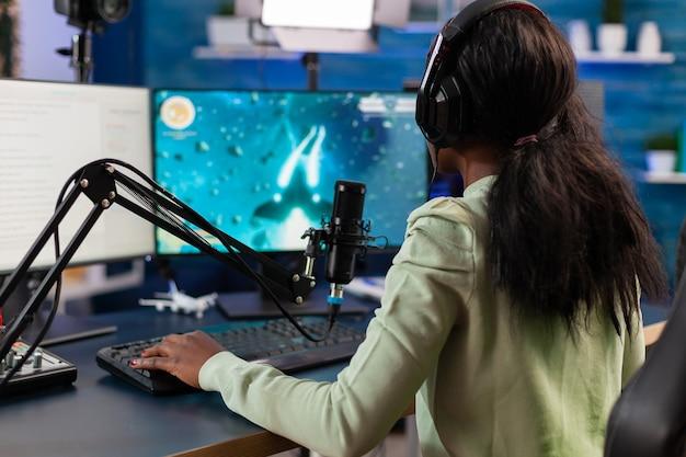 Professionele e-sport afro-gamer die op microfoon praat tijdens live toernooi. virale videogames streamen voor de lol met koptelefoon en toetsenbord of online kampioenschap.