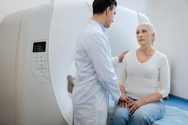 Professionele ervaren mannelijke oncoloog die zijn hand op de schouder van de patiënt legt en haar ondersteunt terwijl hij haar de diagnose vertelt