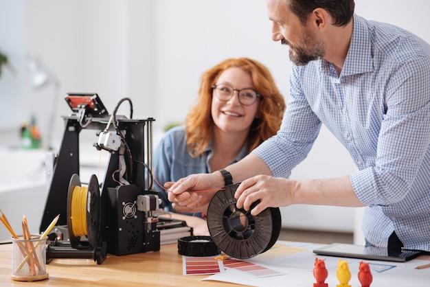 Professionele ervaren mannelijke ontwerper die filament vasthoudt en in 3d-printer laadt terwijl hij met zijn collega werkt