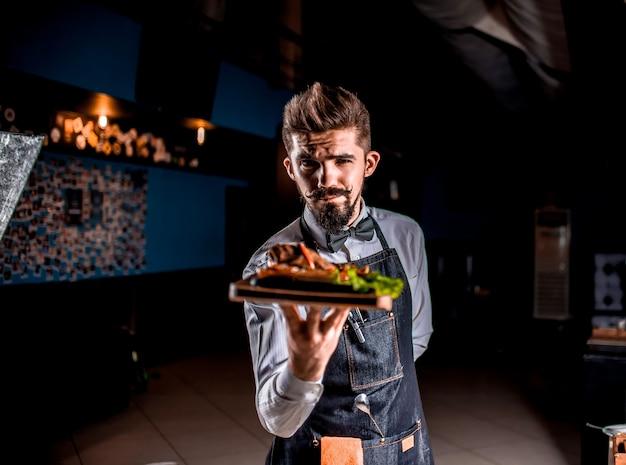 Professionele flunky serveert behulpzaam gekookt gerecht tijdens een feestelijk evenement.
