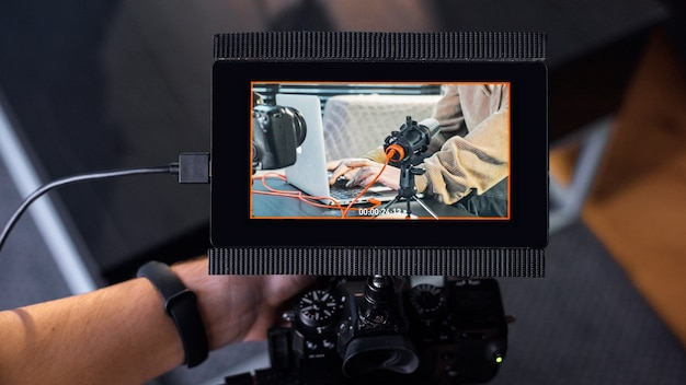 Professionele fotograaf die een camera met extern beeldscherm vasthoudt en een jonge maker van inhoud vastlegt