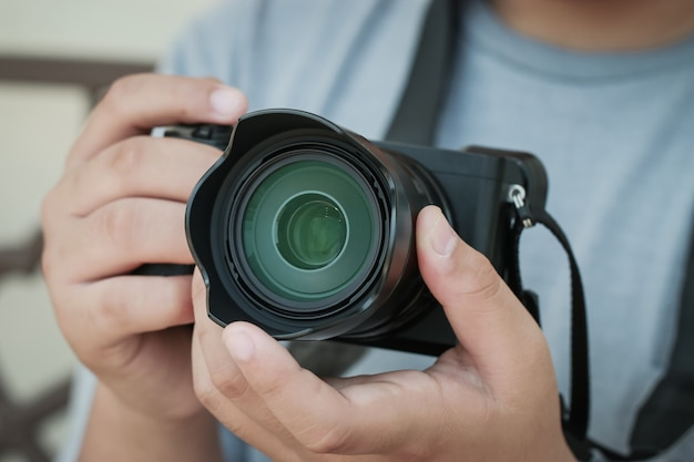 Professionele fotograaf die spiegelloze camera werkt voordat hij fotografeert of foto maakt, lensfocus