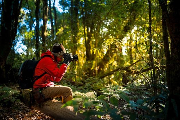 Professionele fotograaf maakt foto's met camera in het bos. reizen, azië, berg,