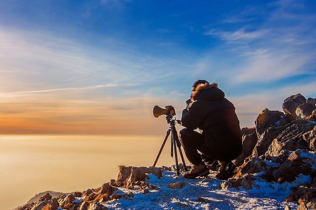 Professionele fotograaf maakt foto's met camera op statief op rotsachtige top bij zonsondergang. donkere toon