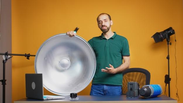 Professionele fotograaf opname presentatie van zilveren beauty dish voor online workshop. professionele studio-video- en fotoapparatuurtechnologie voor werk, fotostudio-ster voor sociale media en invloed