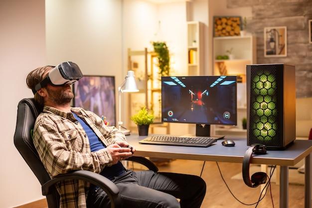 Professionele gamer die een vr-headset gebruikt om 's avonds laat in zijn woonkamer op een krachtige pc te spelen