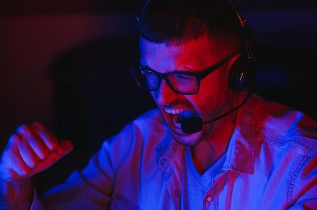 Professionele gamer speelt videogame op zijn computer. hij doet mee aan een online cybergametoernooi of aan een internetcafé. hij draagt een bril en praat in de microfoon.