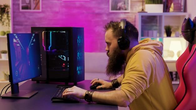 Professionele gamespeler die een koptelefoon draagt in een kamer met kleurrijke neons tijdens het spelen van online videogames.
