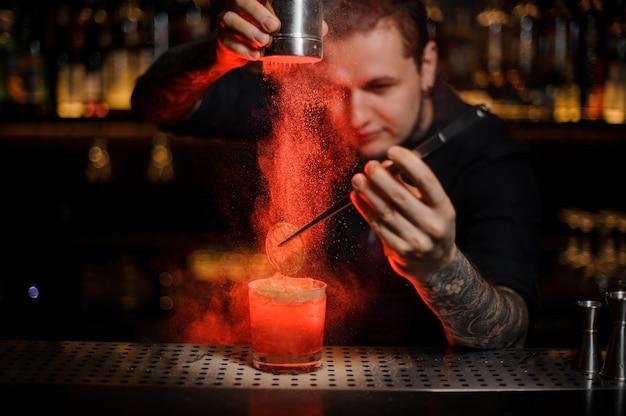 Professionele getatoeëerde barman die aan een alcoholische cocktail in het glas een gedroogde sinaasappel toevoegt met een pincet en aromatisch poeder in het rode licht op de toog.
